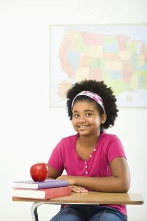 African American girl sitting in school desk smiling at viewer. Stock Photo - 1960728