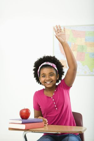 preteen girl: African American girl sitting in school desk raising hand and smiling at viewer.