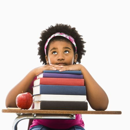 African American girl sitting in school desk with large stack of books looking bored. photo