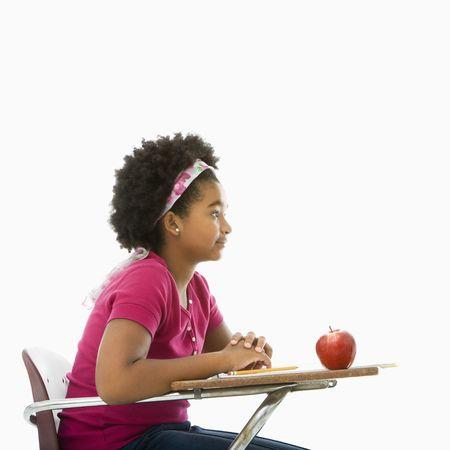 desk: Side view of African American girl sitting in school desk.