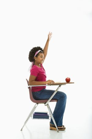 Side view of African American girl sitting in school desk raising hand. Stock Photo