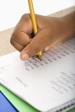 person writing: Hand of African American girl at school desk writing in notebook with pencil. Stock Photo
