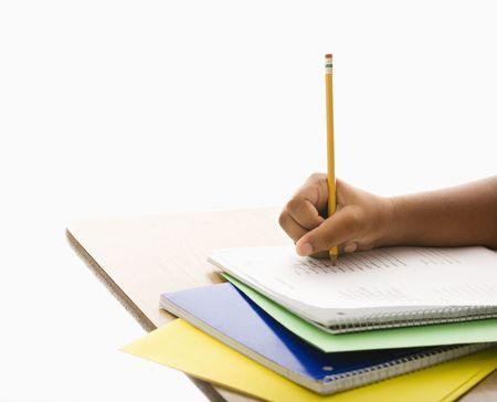 persona escribiendo: Mano de African American ni�a en la escuela escritorio escrito en el bloc de notas con l�piz.  Foto de archivo