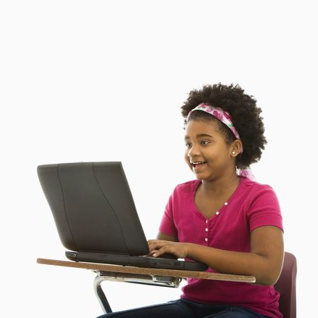 African American girl sitting in school desk typing on laptop computer. Stock Photo - 1960701