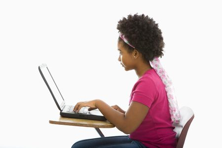 Side view of African American girl sitting in school desk typing on laptop computer. Stock Photo - 1960684