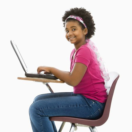 half length posed: African American girl sitting in school desk typing on laptop computer smiling at viewer. Stock Photo