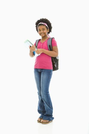 preteen girl: African American girl holding books and wearing backpack smiling at viewer.