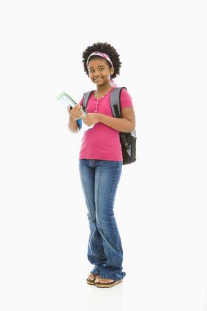 ni�as sonriendo: African American girl la celebraci�n de libros y el uso de mochila al espectador sonriendo.