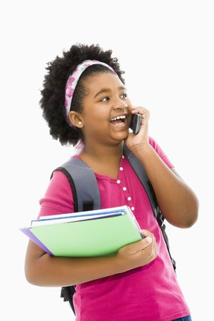 African American girl with books and wearing backpack talking on cell phone. photo