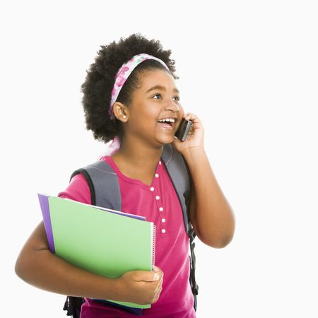 preteen girl: African American girl with books and wearing backpack talking on cell phone. Stock Photo