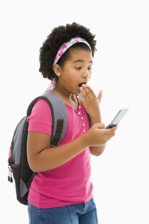 African American girl with backpack looking at cell phone with surprised expression. photo