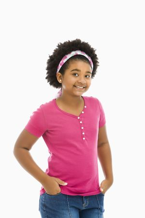 preteen girl: African American girl with hands in pockets wearing headband smiling at viewer.