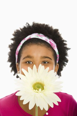 African American girl holding large Gerbera Daisy over face and looking at viewer. Stock Photo - 1960737