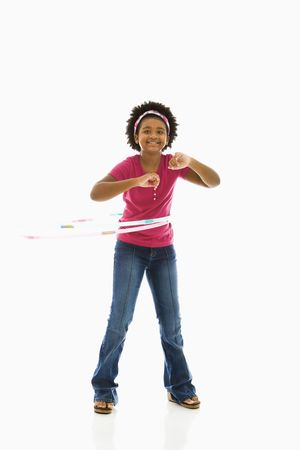 preteen girl: African American girl playing with hula hoop and smiling at viewer.