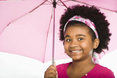 African American girl holding pink umbrella smiling at viewer. photo