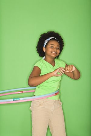 African American girl hula hooping and smiling at viewer. Stock Photo