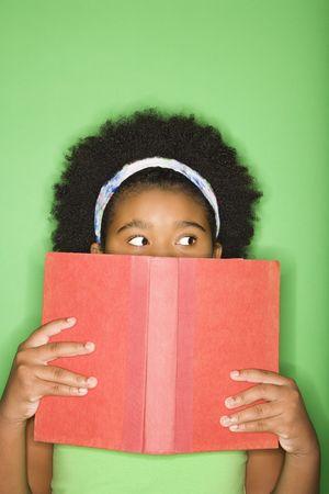 ni�os leyendo: African American ni�a con libro celebrada hasta el rostro mirando sospechosamente a un lado.  Foto de archivo