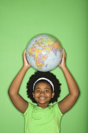 half globe: African American girl holding globe on top of head and smiling at viewer.