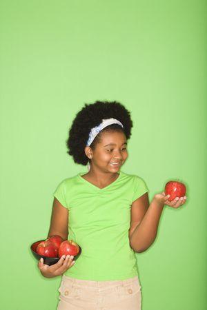ni�as sonriendo: Muchacha americana africana que sostiene manzanas. Foto de archivo