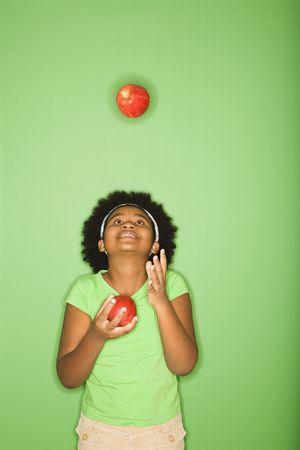 ni�as jugando: Afroamericanas ni�a de malabarismo manzanas.