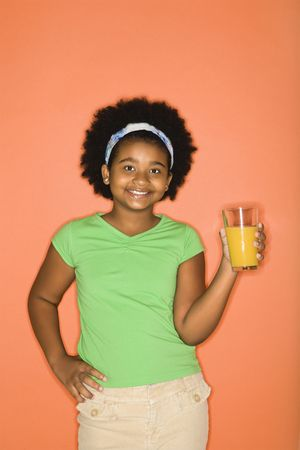 half length posed: African American girl with hand on hip holding glass of orange juice.