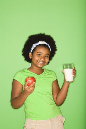 half length posed: African American girl holding glass of milk and apple.