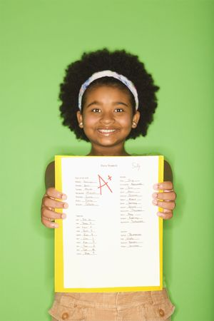 assignment: African American girl holding out graded school assignment smiling proudly at viewer.
