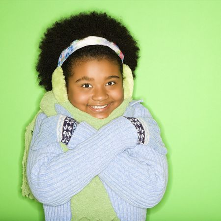 African American girl in winter clothing with arms crossed smiling at viewer. photo