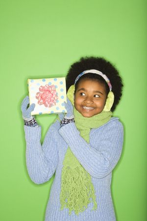 half length posed: African American girl in winter clothing holding wrapped package.