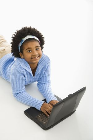 preteen girl: High angle view of African American girl lying on floor using laptop and looking up at viewer.