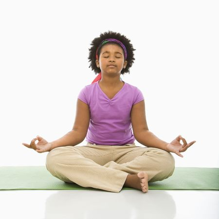 African American girl sitting on floor in yoga lotus posture with eyes closed.