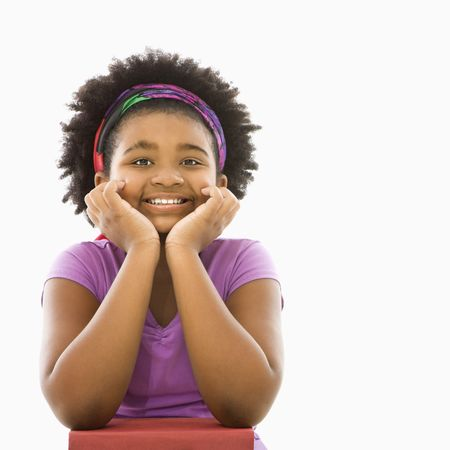 African American girl with head resting on hands smiling at viewer. photo
