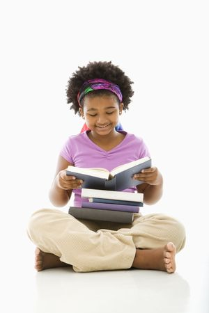 children reading books: African American girl with large stack of books reading. Stock Photo