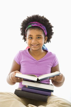 African American girl with large stack of books smiling at viewer. photo