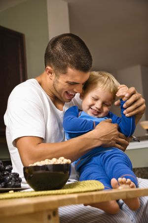 family tickle: Caucasian man tickling toddler son in kitchen. Stock Photo