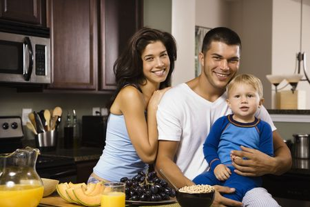 half length posed: Caucasian family with toddler son in kitchen at breakfast smiling at viewer.