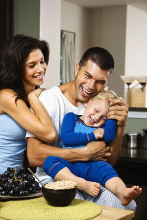 half length posed: Caucasian family with toddler son in kitchen at breakfast smiling and tickling.