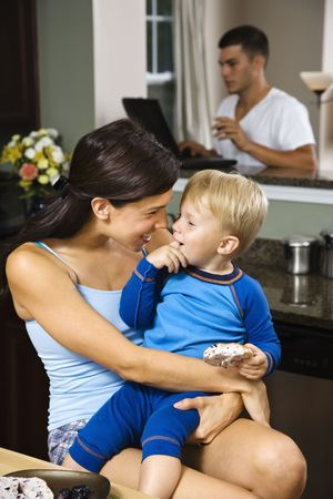 Caucasian woman with toddler son in kitchen with father on laptop in background. Stock Photo - 1960848