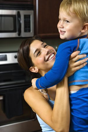 Caucasian woman in kitchen lifting smiling toddler son into the air. Stock Photo - 1960759