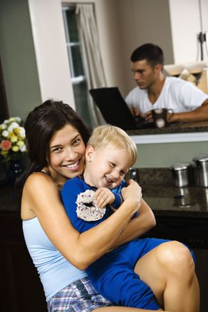 half length posed: Caucasian woman hugging toddler son in kitchen with father on laptop in background.
