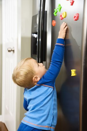 Caucasian toddler boy reaching for magnets on refrigerator.