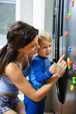 Caucasian toddler boy and mother playing with magnets on refrigerator. photo