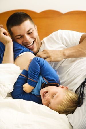 Caucasian toddler boy and father playing and tickling in bed. photo