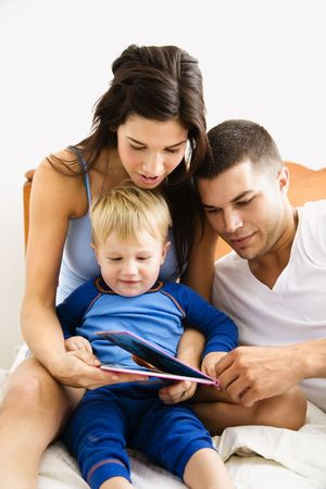Caucasian parents and toddler son reading book in bed. photo