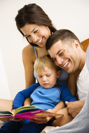 Caucasian parents and toddler son reading book. photo