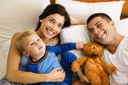 Caucasian parents and toddler son lying in bed smiling. photo