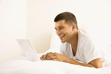 Handsome Caucasian mid adult man lying in bed with laptop. photo
