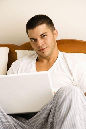 mid adult man: Hermoso mediados de adultos de raza cauc�sica hombre sentado en la cama con el port�til en busca espectador.