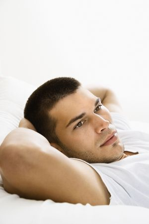 introspective: Handsome Caucasian mid adult man lying with hands behind head.