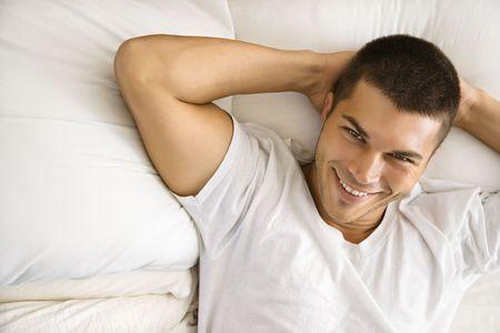 ハイアングルビュー: 成人男性の手笑顔頭の後ろで横になっている半ばハンサムな白人の高角度のビュー。